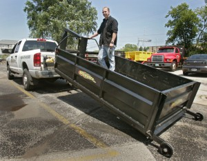 Photo By: MaryJo Walicki --- Doug Bartelt stands in a heavy-duty lifter mounted in the back of his truck.